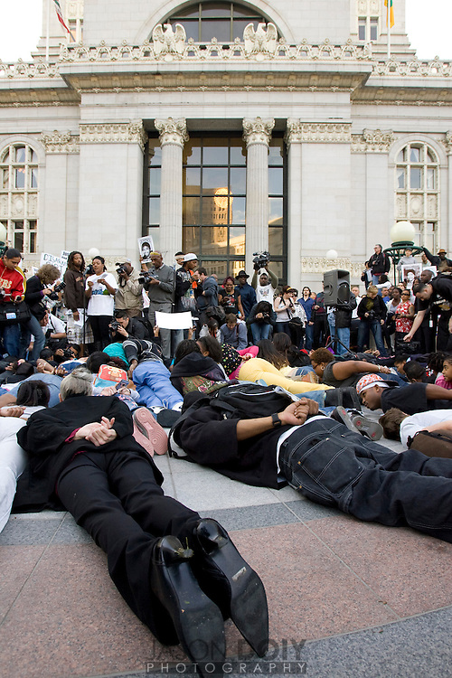 "Dozens of protestors lie down as if under arrest in front of Oakland's City Hall as the names of victims of police shootings are read to a crowd of hundreds. The protest comes hours after attorney Christopher Miller held a press conference in Sacramento on behalf of the Bart Police officer Johannes Mehserle, who was charged with murder for his shooting of Oscar Grant.  Protestors also called for the ""recall, resignation or indictment"" of DA Tom Orloff...Photo by Jason Doiy.1-14-09.047-2009"