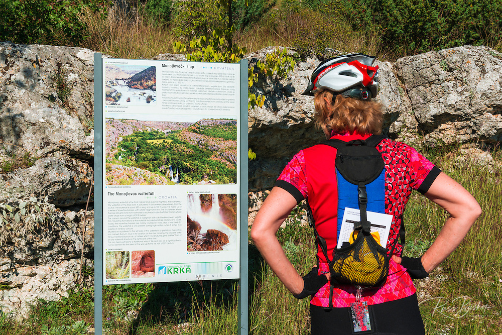 Visitor reading an Interpretive sign at Manojlovac Falls, Krka National Park, Dalmatia, Croatia