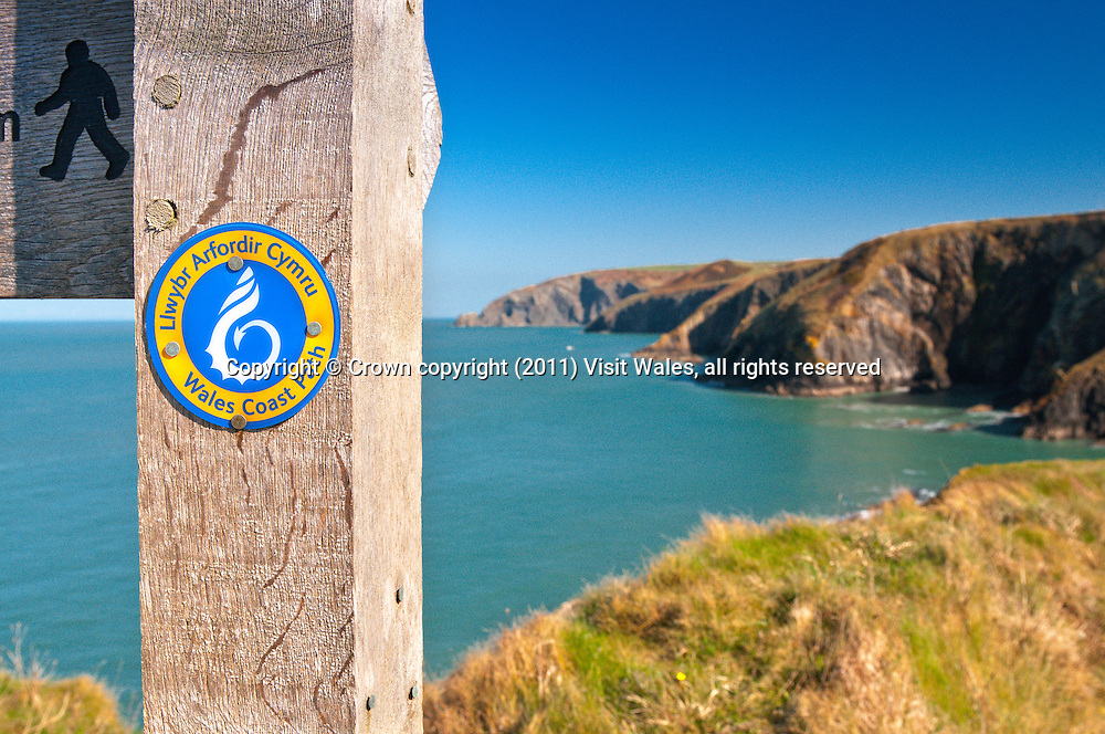 Wales Coast Path sign<br /> Coastline out of focus in background<br /> Ceibwr<br /> Pembrokeshire<br /> South<br /> Walking<br /> Signs