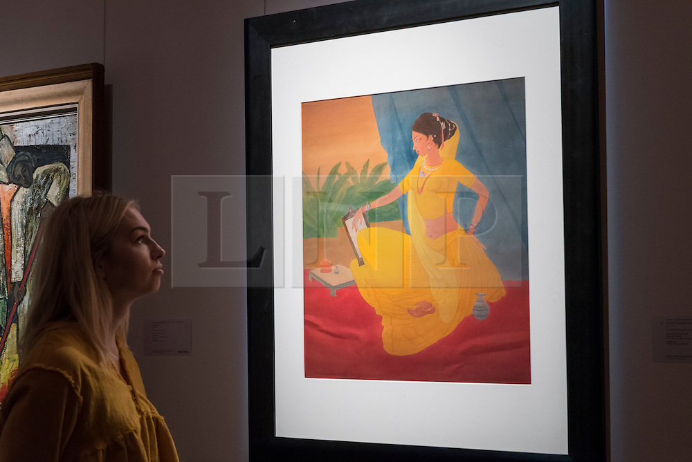 "© Licensed to London News Pictures. 13/10/2016. London, UK. A Sotheby's staff member views ""Untitled (Woman at her Toilette), 1970)"" by Abdur Rahman Chughtai (est. GBP 50-70k) at the preview of Sotheby's Art of the Middle East and India exhibition, which presents artworks to be sold in New Bond Street in four sales in October. Photo credit : Stephen Chung/LNP"