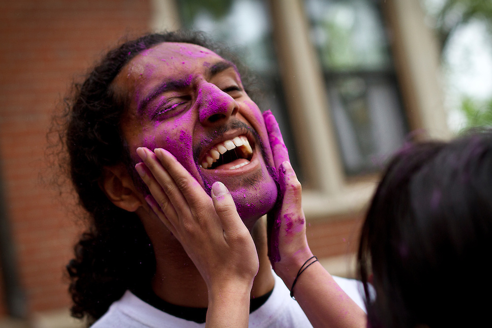 Harpreet Singh reacts to his face being smothered in colors during the Holi celebration at Grinnell College on Saturday.<br />