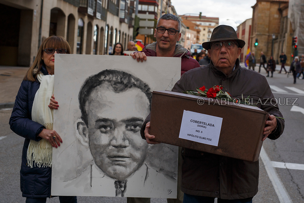 14/04/2018. Relatives hold a coffin containing the remains of victims of Spain Civil War Hipolito Olmo Fernandez and a portrait depicting him along the streets in center of Soria during a homage to hand the remains to their families on April 14, 2018 in Soria, Spain. La Asociacion Soriana Recuerdo y Dignidad (ASRD) 'The Soria Association for Memory and Dignity' celebrated a tribute to hand over the remains of civil war victims to their families. The Society of Sciences of ARANZADI helped with the research, exhumation and identification of the bodies, after villagers passed the information about the mass grave, 81 years after the assassination took place, to the ASRD. Seven people were assassinated around August 25, 1936 by Falangists, as part of General Francisco Franco armed forces, and buried in the 'Fosa de los Maestros' (Teachers Mass Grave) near Cobertelada, Soria, after being taken from prison of Almazan during the Spanish Civil War. Five of them were teachers in the region, and also friends of Spanish writer Antonio Machado. The other two still remain unidentified. Another body was assassinated by Falangists accompanied by a priest in 1936, and was exhumed on 23 September of 2017 near Calata&ntilde;azor, Soria. It belonged to Abundio Andaluz, a politician, lawyer and musician in Soria.<br /> Spain's Civil War took the lives of thousands of people on both sides, and civilians. But Franco continued his executions after the war has finished. Teachers, as part of the education sector, were often a target of Franco's forces. Spanish governments has never done anything to help the victims of the Civil War and Franco's dictatorship while there are still thousands of people missing in mass graves around the country. (&copy; Pablo Blazquez)