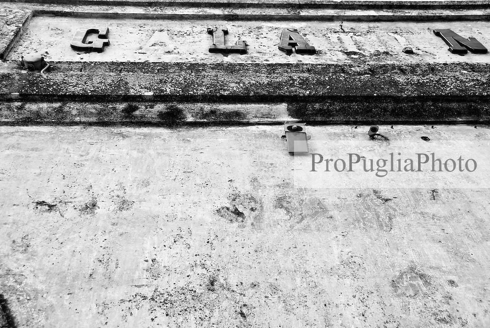 iscrizione oramai decadente della stazione di Galatina, posta all'ingresso laterale in alto con caratteri molto grandi in modo che fossero visibili dal treno in arrivo. Reportage che racconta le situazioni che si incontrano durante un viaggio lungo le linee ferroviarie SUD EST nel salento.