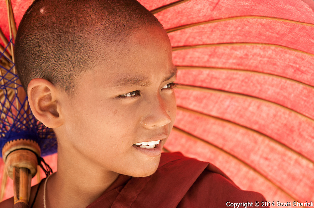 A young monk uses his umbrella to sheild him from the fierce sun in Mingun, Myanmar.