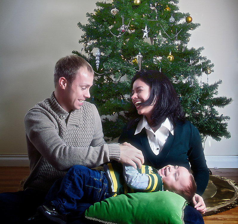 A young family enjoys some laughter in front of a Christmas tree.