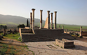 The Capitoline Temple, built 218 AD on the site of an earlier shrine, with an altar (foreground) in a courtyard in front of a 13-stepped platform with a tetrastyle Corinthian column temple, Volubilis, Northern Morocco. The temple was dedicated to Juno, Jupiter and Minerva and was the site of huge civic assemblies. It was reconstructed in 1955 and 1962. Volubilis was founded in the 3rd century BC by the Phoenicians and was a Roman settlement from the 1st century AD. Volubilis was a thriving Roman olive growing town until 280 AD and was settled until the 11th century. The buildings were largely destroyed by an earthquake in the 18th century and have since been excavated and partly restored. Volubilis was listed as a UNESCO World Heritage Site in 1997. Picture by Manuel Cohen