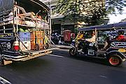 THAILAND, BANGKOK streeet scene, pickup truck and Tuk Tuk passing on a no name street in Bangkok
