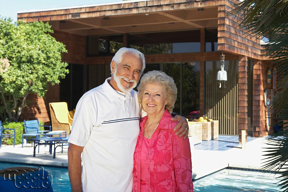 Portrait of senior couple outside house