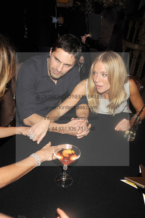 OLIVIER MARTINEZ and SIENNA MILLER at a party to celebrate the launch of Hollywood Domino - a brand new board game, held at Mosimann's 11b West Halkin Street, London on 7th November 2008.  The evening was in aid of Charlize Theron's Africa Outreach Project.