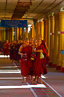 Procession of monks walking through hallway in the Kya Khat Winne Monastery, Bago, Myanmar (Burma)