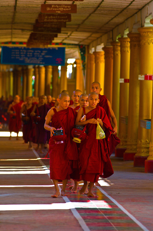 Procession of monks walking through hallway in the Kya Khat Winne Monastery, Bago, Myanmar (Burma)