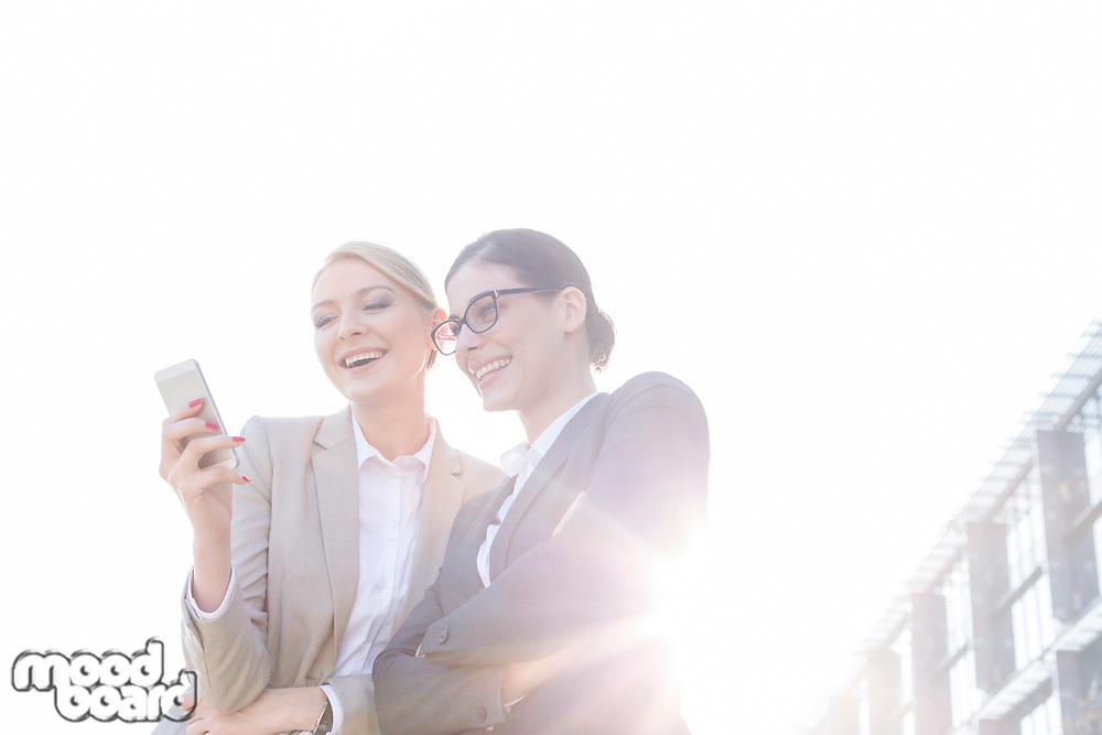 Low angle view of happy businesswomen using smart phone against clear sky on sunny day