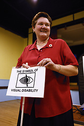 Disabled woman speaker at Disability Awareness Forum; showing a visual disability symbol,