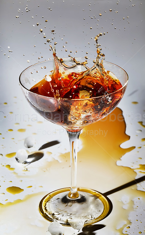 Ice splash inside glass with cocktail. This file is only available at Stockfood.com and can be purchased at this address: https://goo.gl/BM5qD7