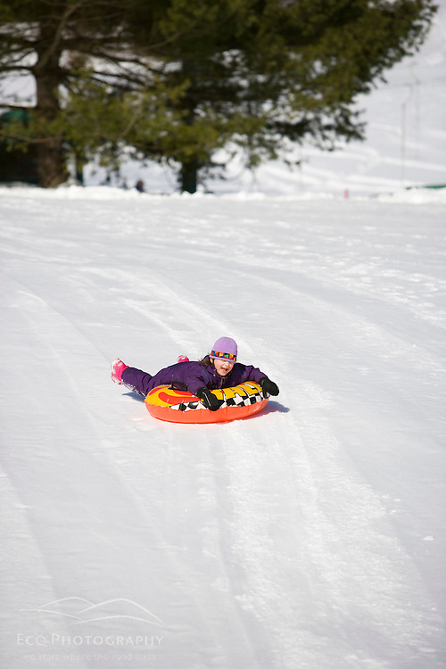 A young girl (age 6) rides her snow tube down a  hill in Quechee, Vermont. Model Release.