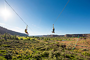 Two boys ride side by side together while zip lining in the Snake River Canyon with Zip the Snake in Twin Falls, Idaho. MR