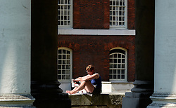 © Licensed to London News Pictures. 25/07/2012. London, UK .  A woman relaxes and reads a book in the sunshine as temperatures reach 30 degrees at Greenwhich Navel Academy in London today 25 July 2012. Photo credit : Stephen Simpson/LNP