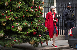 © Licensed to London News Pictures. 04/12/2018. London, UK. London, UK. Prime Minister Theresa May emerges from behind the Downing Street Christmas tree as she leaves for Parliament. Today the House of Commons will start the first of five days of debate on the Brexit withdrawal agreement.  Photo credit: Peter Macdiarmid/LNP