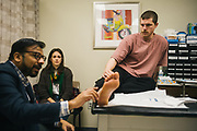 "BIRMINGHAM, AL – FEBRUARY 1, 2019:  Accompanied by his girlfriend Noel Morse (center), Warren ""Azad"" Stoddard (right), 24, receives medical treatment for a gunshot wound he suffered while fighting ISIS alongside Kurdish YPG forces in Syria. CREDIT: Bob Miller for The New York Times<br /> <br /> In the war against ISIS, American volunteers have joined the ranks of a Syrian militia, operating independently of the United States. Until recently, the predominantly Kurdish YPG forces had enjoyed air and ground support from the United States, but now that US is officially leaving, the remaining American volunteers face uncertain odds. <br /> <br /> Warren Stoddard, 24, comes from a long line of military veterans and active service members. So when a knee injury prevented him from enlisting in the Marines in 2016, he reached out to a YPG liaison on Facebook to declare his interest in volunteering. ""I always wanted to serve, to do something worthwhile and to take part in some historical event,"" Stoddard said. ""And I cared about the Kurdish cause."" Two years later, as the Turkish invasion placed added pressure on the predominantly Kurdish YPG, Stoddard finally received an invitation to join and purchased his own one way ticket. Six months later, while engaging an ISIS stronghold alongside his YPG unit, Stoddard caught bullet fragments in his his upper thigh and foot, where a small fragment is still lodged."