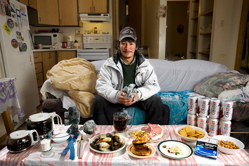 Willie Ishulutak, an Innuit soapstone carver in Iqaluit, Nunavut, Canada with one day's typical food, and drink. (From the book What I Eat, Around the World in 80 Diets.) The caloric value of his day's worth of food on a typical day in the month of October was 4700 kcals. He is 29 years of age; 5 feet,  9 inches and 143 pounds. Carving is one of the few traditions of the Inuit that has made the leap into the wage-earning modern world. Willie says he can complete two or three pieces in a day, then sell them in the evening at bars and restaurants in Iqaluit for $100 ($93 USD) each, and sometimes more. MODEL RELEASED.