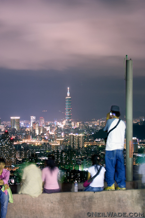 People gaze on the nighttime skyline of Taipei City in Taiwan.