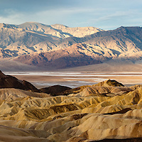 Death Valley National Park, California Manly Beacon at sunrise with Badwater Basin, -279 ft, the lowest spot in all of North America, and snow capped Telescope Peak, 11,043 ft, the highest peak in Death Valley National Park, show a stark contrast. Panorama stitched in Lighroom