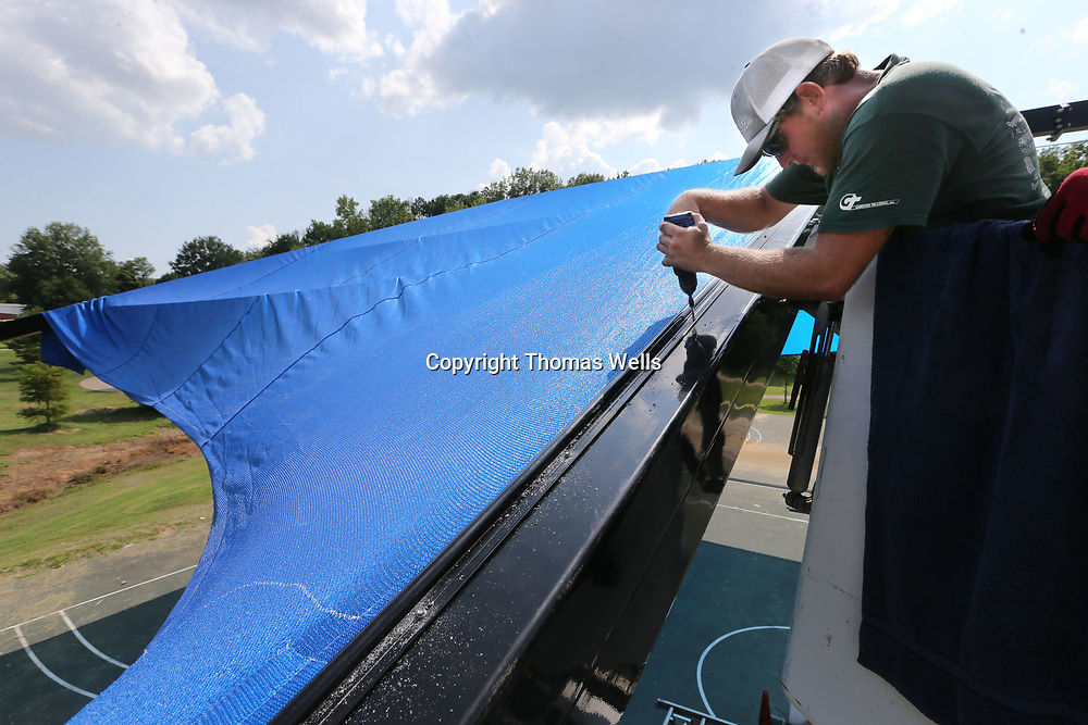David Singleton uses self tapping metal screws to secure the center edge of the new covering of the basketball courts at Gumtree Park on Front Street.