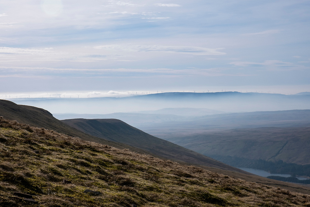 A line of wind turbines in the horizon on the top of Rhigos Hill Pass in the Cynon Valley, Rhondda Cynon Taf, South Wales, United Kingdom. There are 76 turbines creating a 228M Renewable Energy Wind Farm.  The view is from Pen Y Fan Mountain and looks over the Rhondda Valley on a  misty day.  (photo by Andrew Aitchison / In pictures via Getty Images)