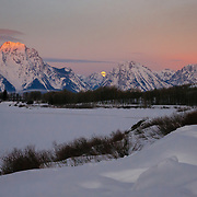 Craggy Mount Moran towers over trees and snowfields as a full moon sets in Grand Teton National Park, Wyoming.