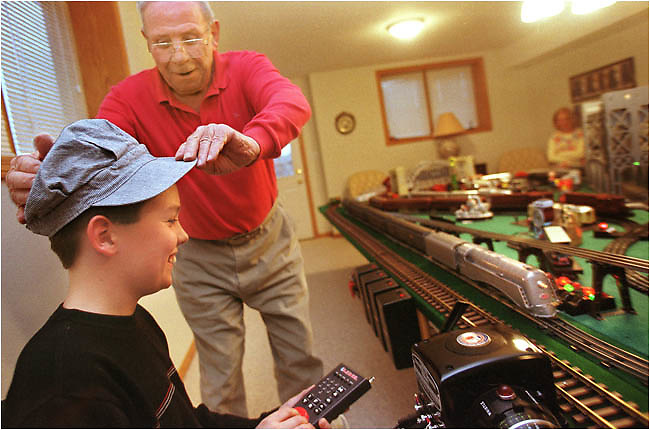 Saniel Laplace, 81, of Iowa City, places his conductor cap on the head of his neighbor Isaac DeJong, 11, of Iowa City, as they operate model trains in the basement of his home Tuesday Dec. 2, 2003 in Iowa City. DeJong comes over about once a month to visit with Saniel and run the model trains.