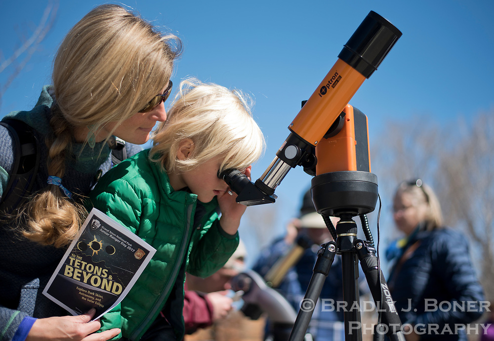 Lauren Hugo, of Alta, helps her son, Olin, 5, look at the sun with a specially-equipped lens for solar viewing during Junior Ranger Day at the Craig Thomas Discovery and Visitor Center in Grand Teton National Park.
