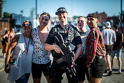 © Licensed to London News Pictures . 25/08/2019. Manchester, UK. An armed police officer on patrol at the venue poses with fans of Ariana Grande and other musical acts , as they gather at Mayfield Depot ahead of performances this evening . Manchester's annual Gay Pride festival , which is the largest of its type in Europe , celebrates LGBTQ+ life . Photo credit: Joel Goodman/LNP