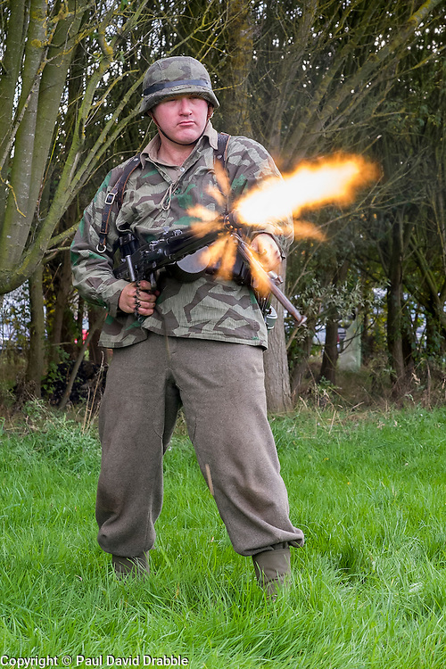 Re-encator portraying a German panzer grenadier test fires fires a 'section' 5 MG42 machinegun from the hip during the Pickering Wartime weekend on the Pickering Showground<br /> <br /> 17/18 October 2015<br />  Image &copy; Paul David Drabble <br />  www.pauldaviddrabble.co.uk