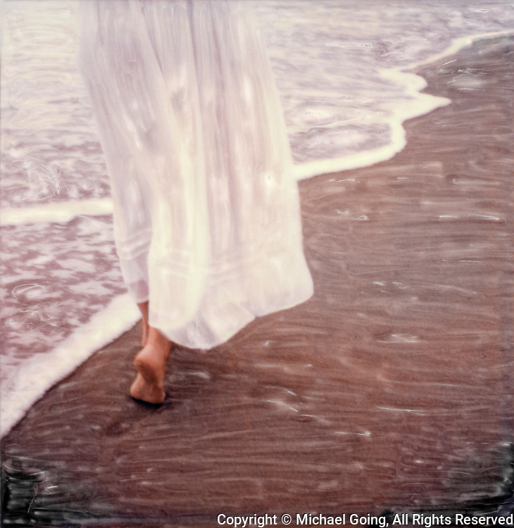 Woman walking in bare feet on sand with full length white cotton dress
