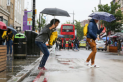 © Licensed to London News Pictures. 30/07/2019. London, UK. A tourist steps in a puddle of rain water in Camden Market, north London after heavy rainfall. Photo credit: Dinendra Haria/LNP