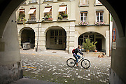 03 AUGUST 2007 -- BERN, SWITZERLAND: A bicyclist rides past porticos down a street in Bern, the federal capital of Switzerland. The city was founded in the 12th century by Berchtold V, Duke of Zahringen, who established a fort on the site of the present day city. Because of its well maintained downtown core, preserved arcades and fountains, Bern is a UNESCO World Heritage Site. Photo by Jack Kurtz/ZUMA Press