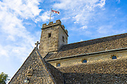 English flag of St George on old stone tower of St Mary's Church, Swinbrook, The Cotswolds, England, UK