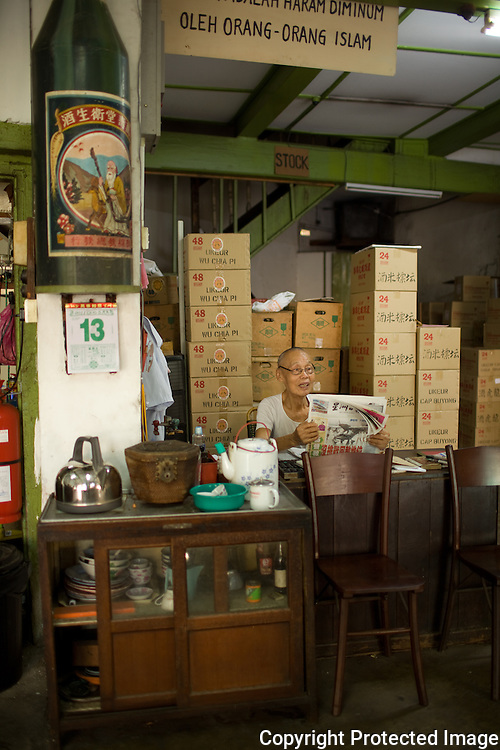 A chinese spirits dealer in his shop on Pantai street