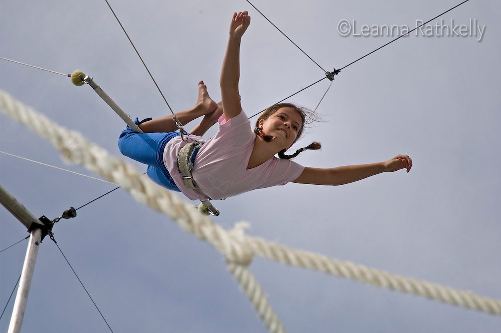 A girl, 10-12, swings from the trapeze bar at Blackcomb Mountain, Whistler, BC Canada