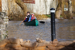 © Licensed to London News Pictures. 09/02/2014. Winchester, Hampshire, UK. People paddling in their canoe in River Park in Winchester. Water levels rose overnight in parts of the historic city where a flood warning has been issued by the Environment Agency for parts of the River Itchen. Photo credit : Rob Arnold/LNP