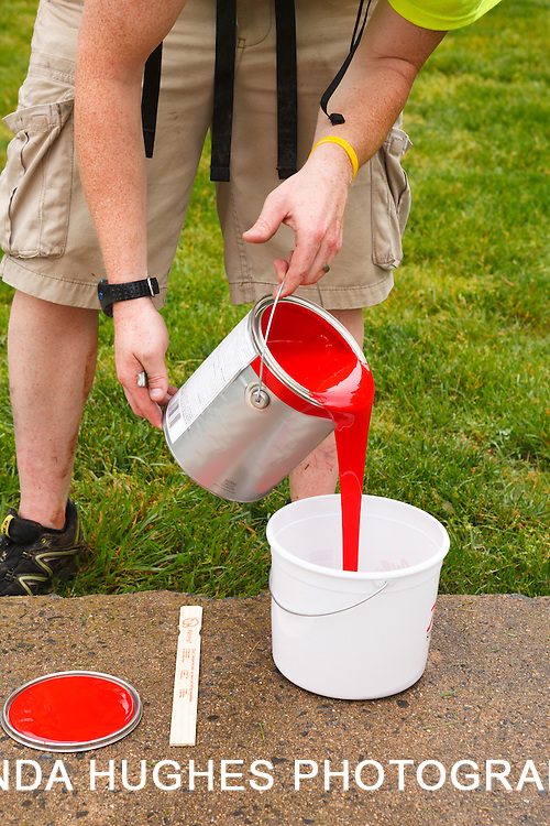 Man pouring red paint