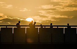 © Licensed to London News Pictures. 16/10/2017. London, UK. Communters cross London Bridge at sunrise, as the remnants of Hurricane Ophelia heads for the British Isles. Winds of up to 80mph are expected in some parts of the UK. Photo credit: Ben Cawthra/LNP