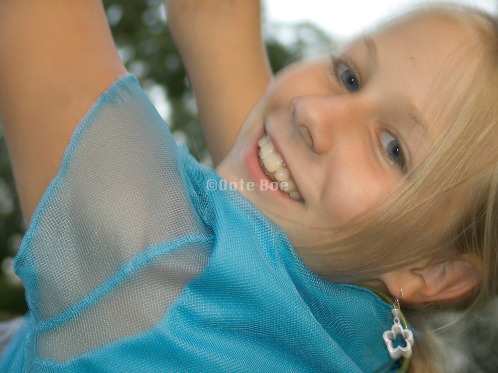 close up of a young girl on a swing