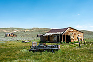 A wooden buckboard or wagon sits abandoned in grass outside a decrepit house or barn at Bodie State Historic Park, a ghost town in California.