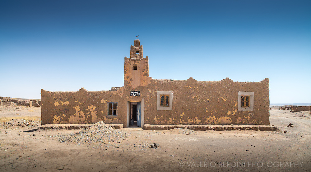 A mosque built in the characteristic Moroccan architecture made with mud in a tiny village at the edge of Sahara desert in Erg Chebby, near Merzouga.