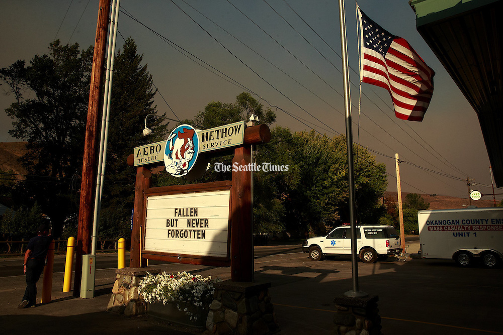 An  EMT stands outside Aero Methow Rescue Services after ambulances carried the bodies of three fallen firefighters from Twisp to Omak, Washington during a procession Thursday, Aug. 20, 2015.<br />