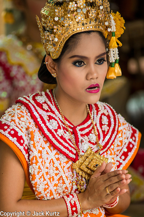 27 SEPTEMBER 2012 - BANGKOK, THAILAND:  A Thai classical dancer at the Erawan Shrine in Bangkok. People pay for dances while they pray in the belief that the dancers will help their prayers be heard. The Erawan Shrine is a Hindu shrine in Bangkok, Thailand, that houses a statue of Phra Phrom, the Thai representation of the Hindu creation god Brahma. A popular tourist attraction, it often features performances by resident Thai dance troupes, who are hired by worshippers in return for seeing their prayers at the shrine answered. The Erawan Shrine was built in 1956 as part of the government-owned Erawan Hotel to eliminate the bad karma believed caused by laying the foundations on the wrong date. The hotel's construction was delayed by a series of mishaps, including cost overruns, injuries to laborers, and the loss of a shipload of Italian marble intended for the building. Furthermore, the Ratchaprasong Intersection had once been used to put criminals on public display. An astrologer advised building the shrine to counter the negative influences. The Brahma statue was designed and built by the Department of Fine Arts and enshrined on 9 November 1956. The hotel's construction thereafter proceeded without further incident. In 1987, the hotel was demolished and the site used for the Grand Hyatt Erawan Hotel.      PHOTO BY JACK KURTZ