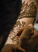 A Henna / Mehndi artist working on a bride's arm during a Henna party. The Elephant figure is Ganesha, one of the best known and most worshipped dieties of the Hindu pantheon.