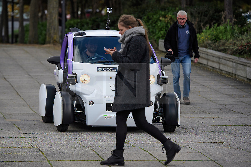 © London News Pictures. 11/10/2016. Milton Keynes, UK. A woman using her mobile phone steps out in front of a driverless car being tested around pedestrian areas in Milton Keynes in the first public test of autonomous electric vehicles in the UK. The vehicles have been developed by the Oxford Robotics Institute and Oxbotica. Photo credit: Ben Cawthra/LNP