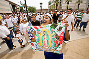 """10 APRIL 2006 - PHOENIX, AZ: A Mexican immigrant waves a Virgin of Guadalupe flag while he chants """"Si Se Puede"""" (""""Yes We Can"""") during an immigrants' rights march in Phoenix, AZ. More than 200,000 people participated in a march for immigrants's rights in Phoenix Monday. The march was a part of a national day of action on behalf of undocumented immigrants. There were more than 100 such demonstrations across the US Monday. Protestors were encouraged to wear white, to symbolize peace, and wave American flags, to demonstrate their patriotism to the US.  Photo by Jack Kurtz"""